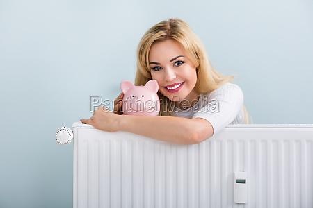 happy woman with piggybank on radiator