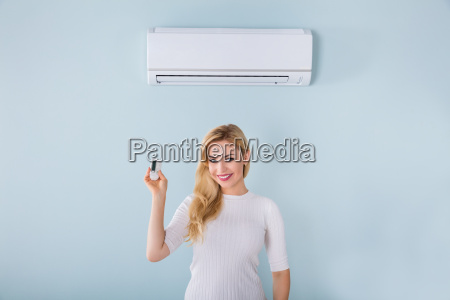 woman holding remote controller of air