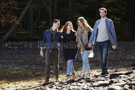 four people walking along couples hand