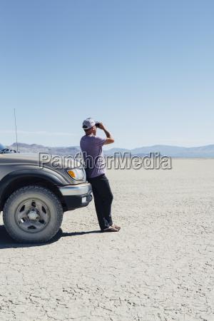 man standing on vast desert looking