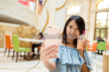 woman taking photo with her drink
