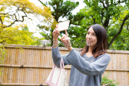 woman taking photo by mobile phone