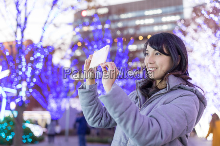 woman taking photo with christmas decoration