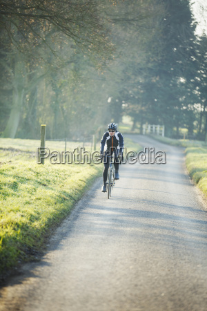 a cyclist pedalling along a country