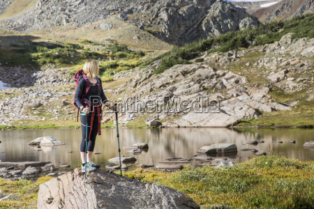 young woman standing on rock exploring