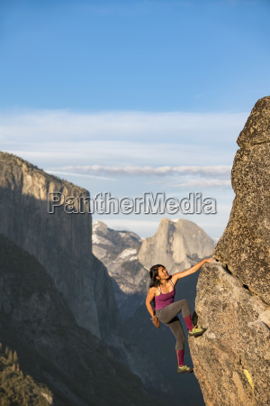 female climber climbing on rock in