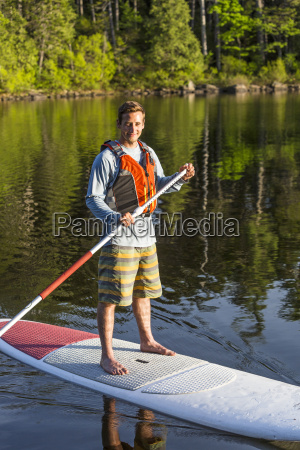 ein mann paddleboarding auf langer teich