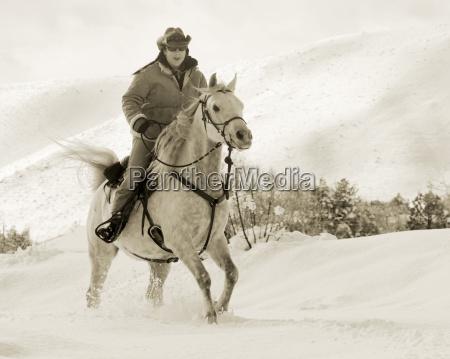 woman gallops through the snow on