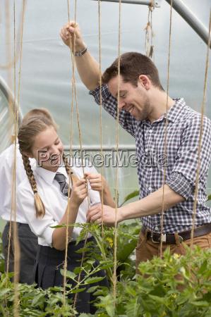 male teacher and schoolgirl learning gardening