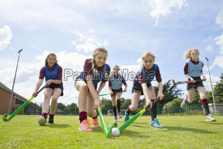 middle schoolgirls running playing field hockey