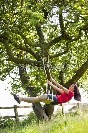 happy woman swinging on tree swing