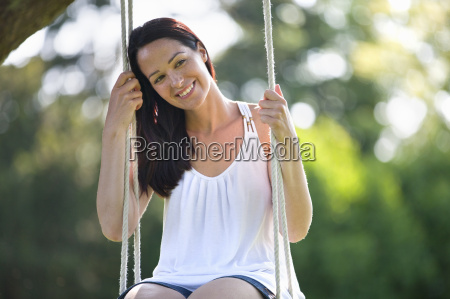 portrait happy brunette woman swinging on