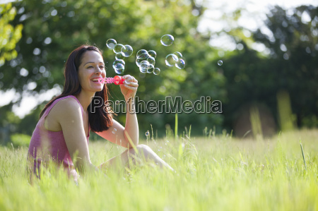 happy woman blowing bubbles with bubble