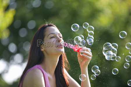 carefree happy woman blowing bubbles with