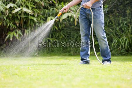 man using hose watering green lawn