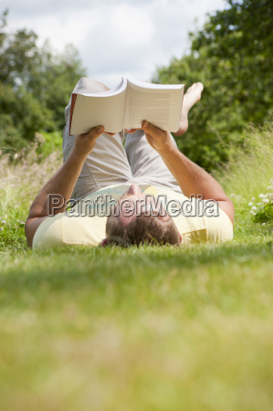 man reading book relaxing in sunny