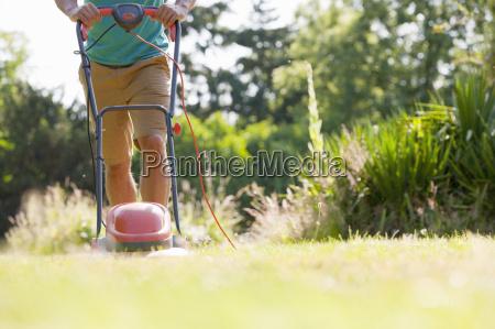 man pushing lawn mower mowing grass