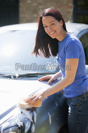 portrait happy woman washing car with