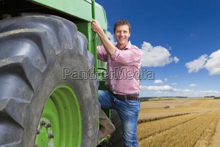 portrait of farmer climbing into cab