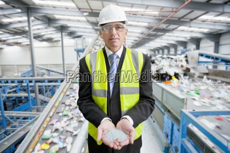 geschaeftsmann in der recycling anlage halten