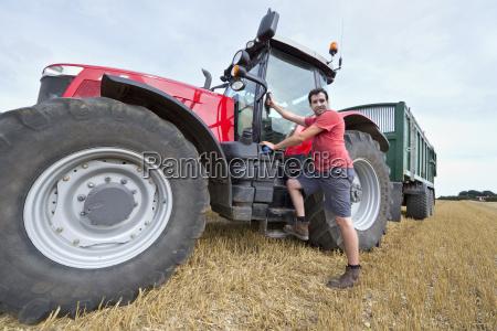 farmer climbing into cab of tractor