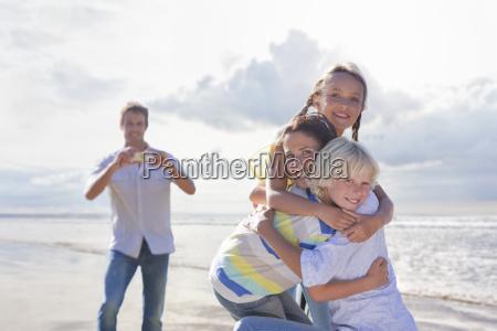 family taking photos on beach vacation