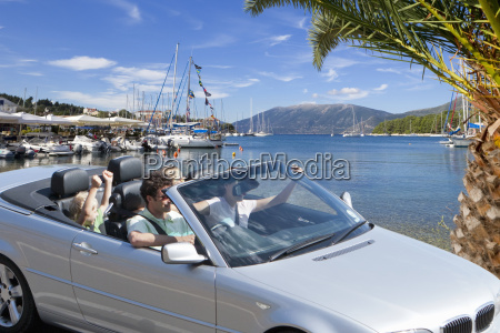 family driving in convertible car on