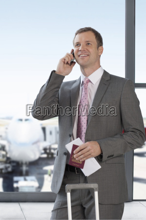 businessman with luggage making phone call