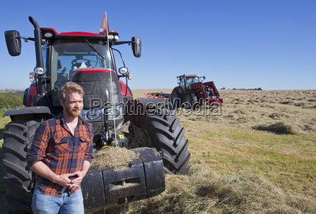 farmer standing next to tractor making