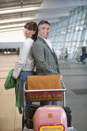 mature couple with luggage in airport