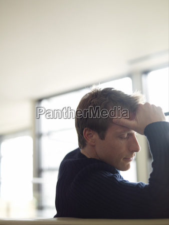 portrait of man holding head