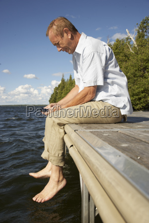 man on dock with cellular phone