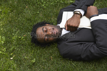 businessman lying in the grass