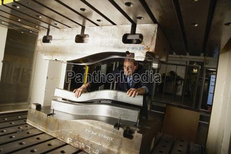 man with metal press