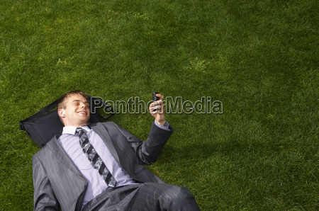 businessman lying on grass reading text