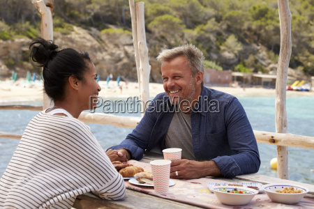 middle aged couple sitting at table