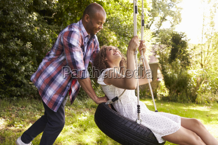 man pushing woman on tire swing