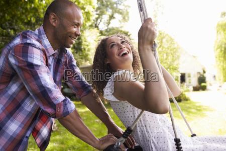 side view of man pushing woman