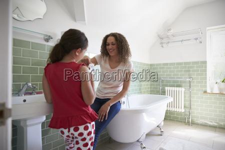 tochter zaehneputzen im badezimmer mit mutter
