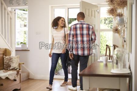 man opens front door for woman