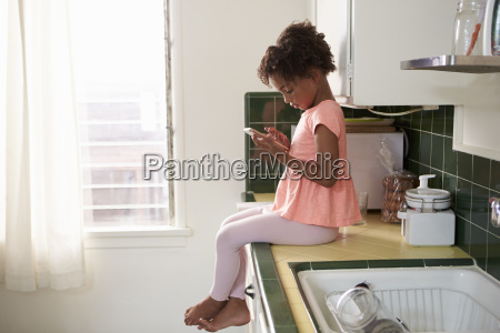 young girl sits in kitchen and