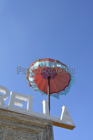 fringed parasol at roof of a