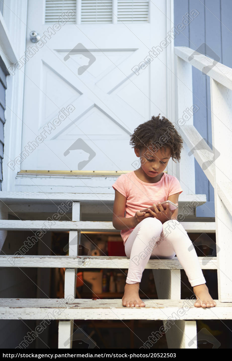 young, girl, sits, on, outdoor, steps - 20522503