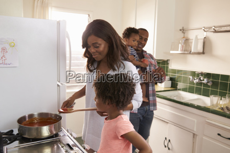family at home preparing meal in