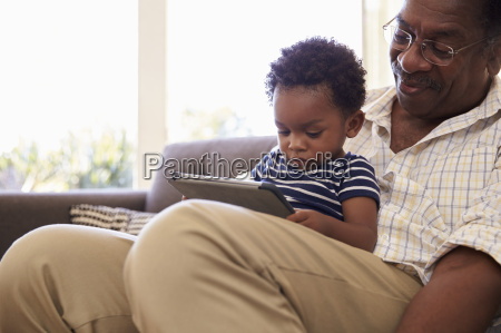 grandfather and grandson at home using