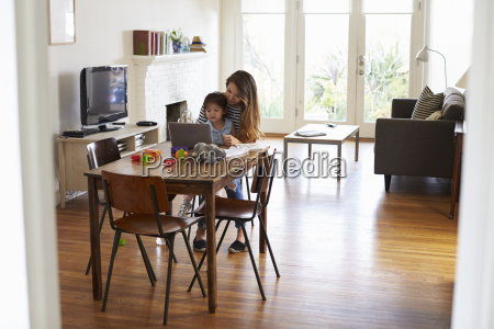 mother and daughter using laptop at