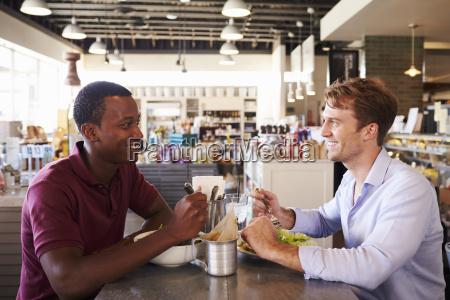 two men enjoying lunch in delicatessen