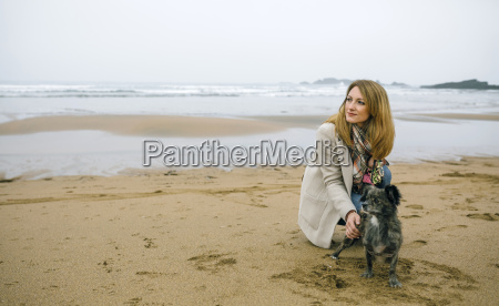 woman stroking dog on the beach