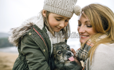 mother and daughter stroking their dog