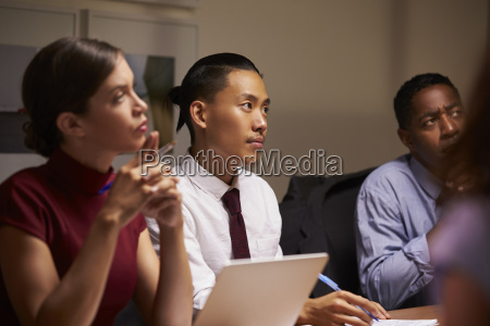 business colleagues listening at evening meeting